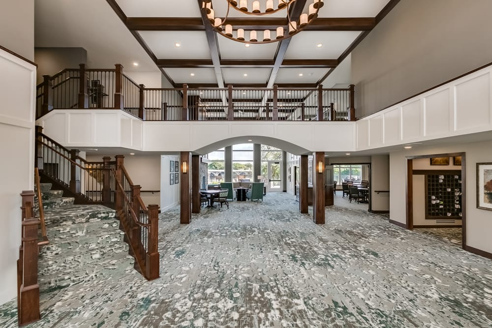 Large lobby with a staircase at Applewood Pointe of Champlin at Mississippi Crossings in Champlin, Minnesota.