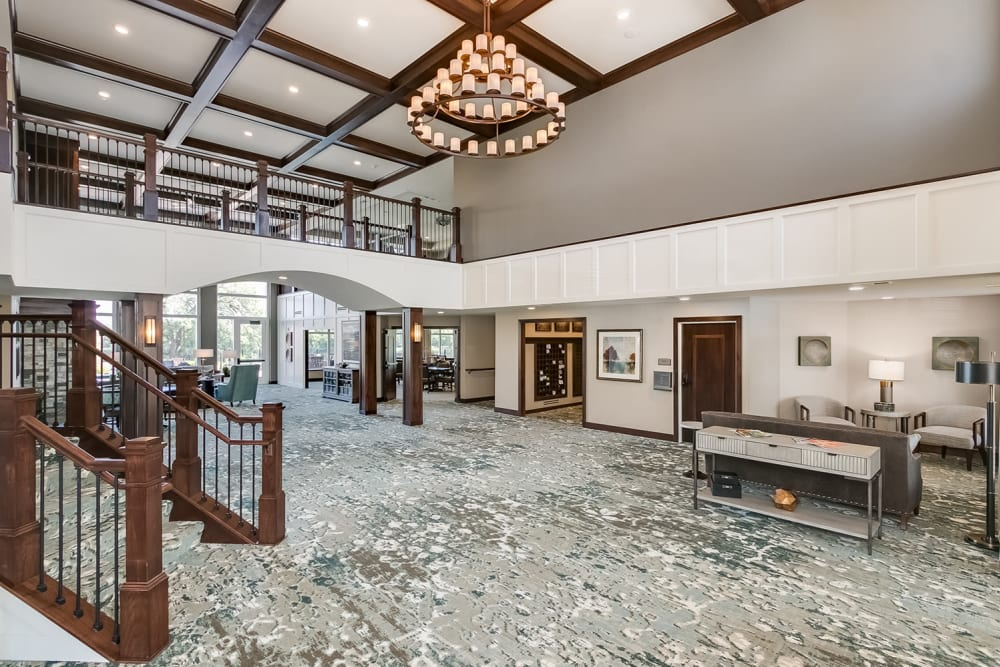 Lobby with seating area and a chandelier at Applewood Pointe of Champlin at Mississippi Crossings in Champlin, Minnesota.