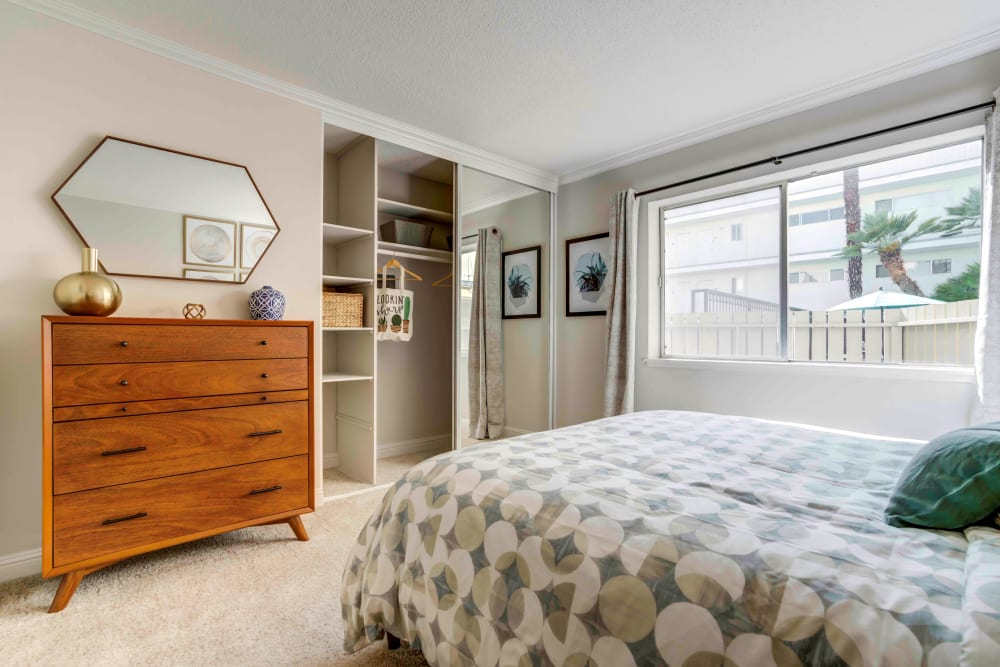 Well-furnished master bedroom with plush carpeting in a model home at Sofi Redwood Park in Redwood City, California