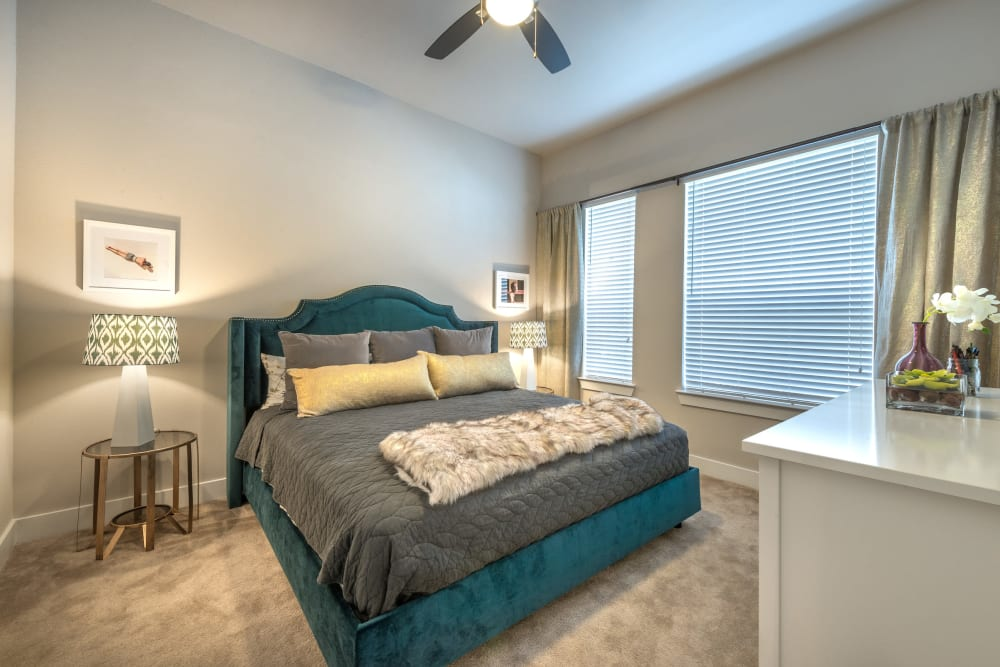 Model home's master bedroom with a ceiling fan and plush carpeting at Olympus at Ross in Dallas, Texas