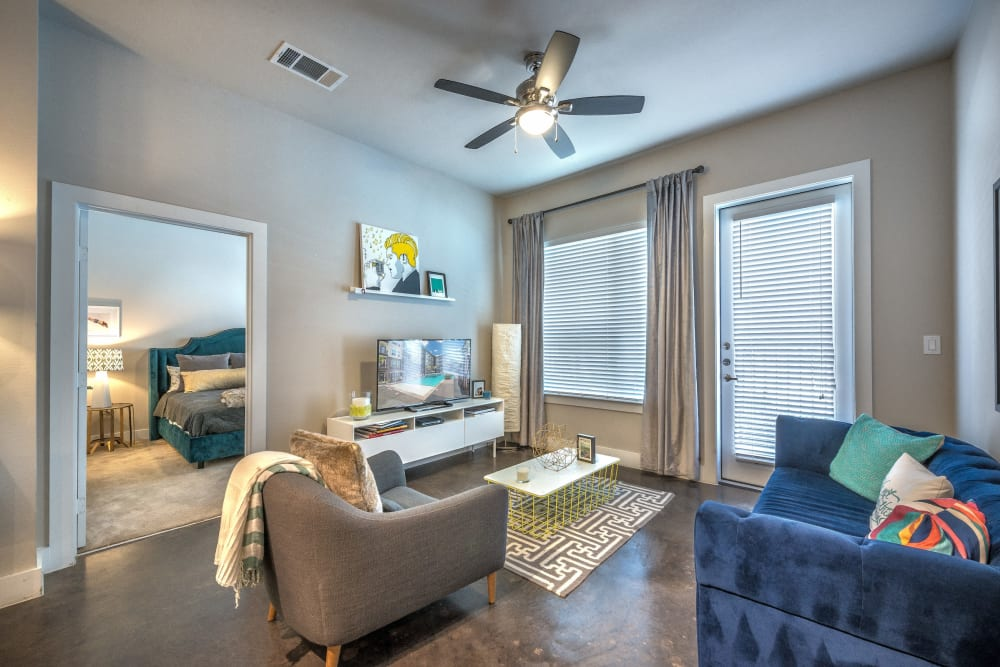 Modern decor and a ceiling fan in a model home's living area at Olympus at Ross in Dallas, Texas