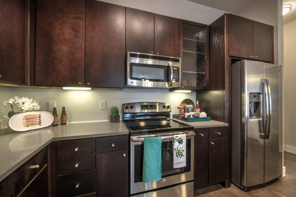 Rich, dark wood cabinetry and stainless-steel appliances in a model home's kitchen at Olympus at Ross in Dallas, Texas