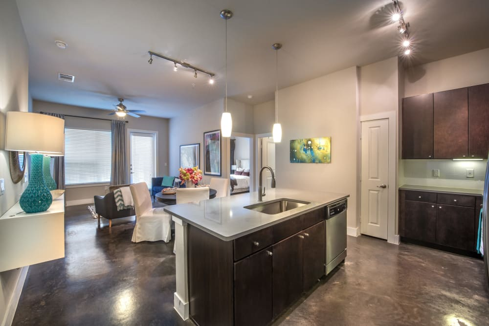 Island with quartz countertop and stained-concrete flooring in a model home's kitchen at Olympus at Ross in Dallas, Texas