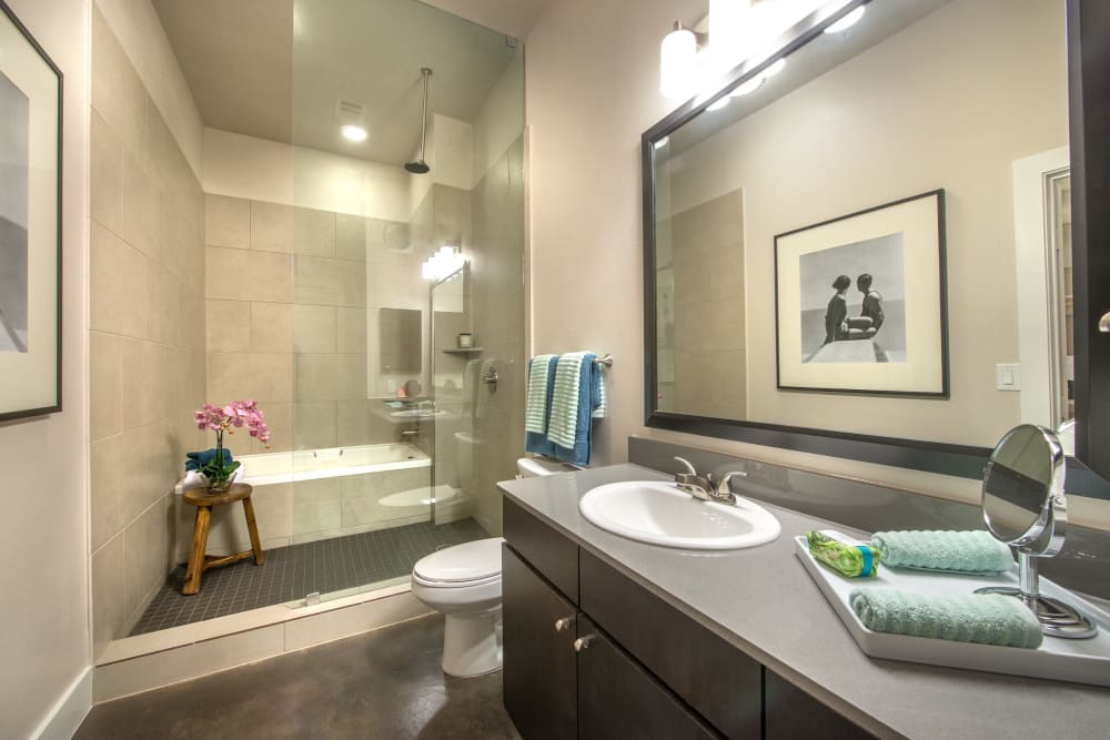 Luxurious bathroom with walk-in shower and quartz countertop in a model home at Olympus at Ross in Dallas, Texas