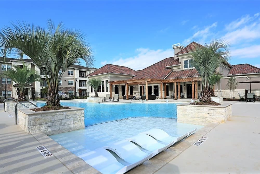 Resort-style swimming pool with palm trees at Trails at Lake Houston in Houston, Texas