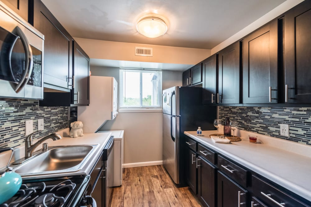 Dark wood kitchen cabinetry with stainless steel appliances at The Blvd at White Springs in Nottingham, Maryland
