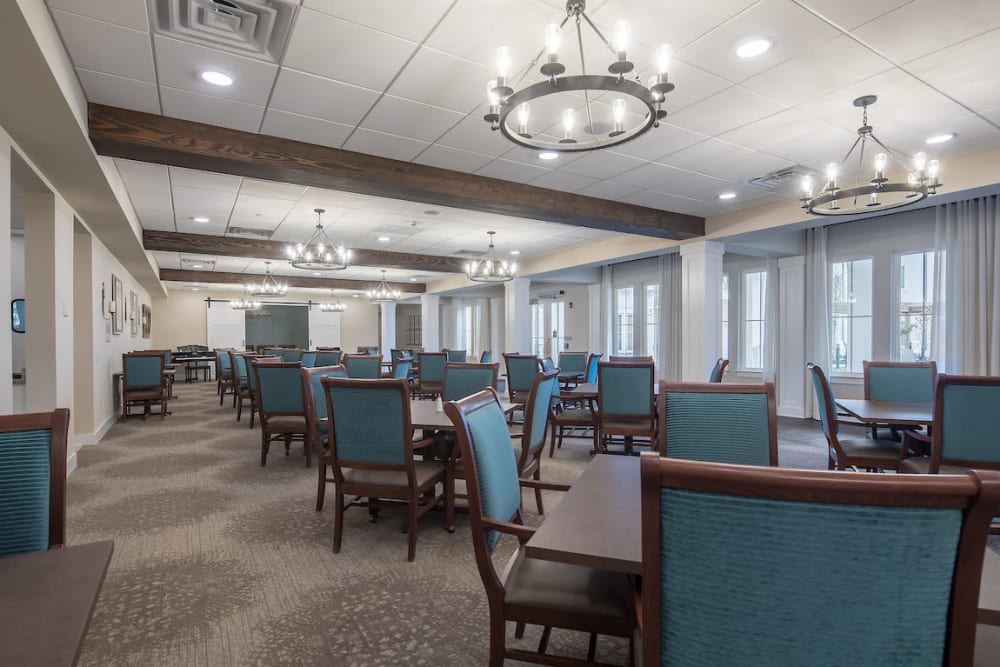 Elegant dining room with large windows at The Claiborne at Gulfport Highlands in Gulfport, Mississippi.