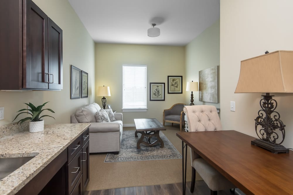 Resident apartment with kitchenette and living room at The Claiborne at Shoe Creek in Baton Rouge, Louisiana.