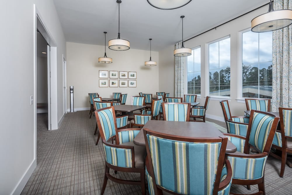 Comfy dining area with large windows at The Claiborne at Shoe Creek in Baton Rouge, Louisiana.