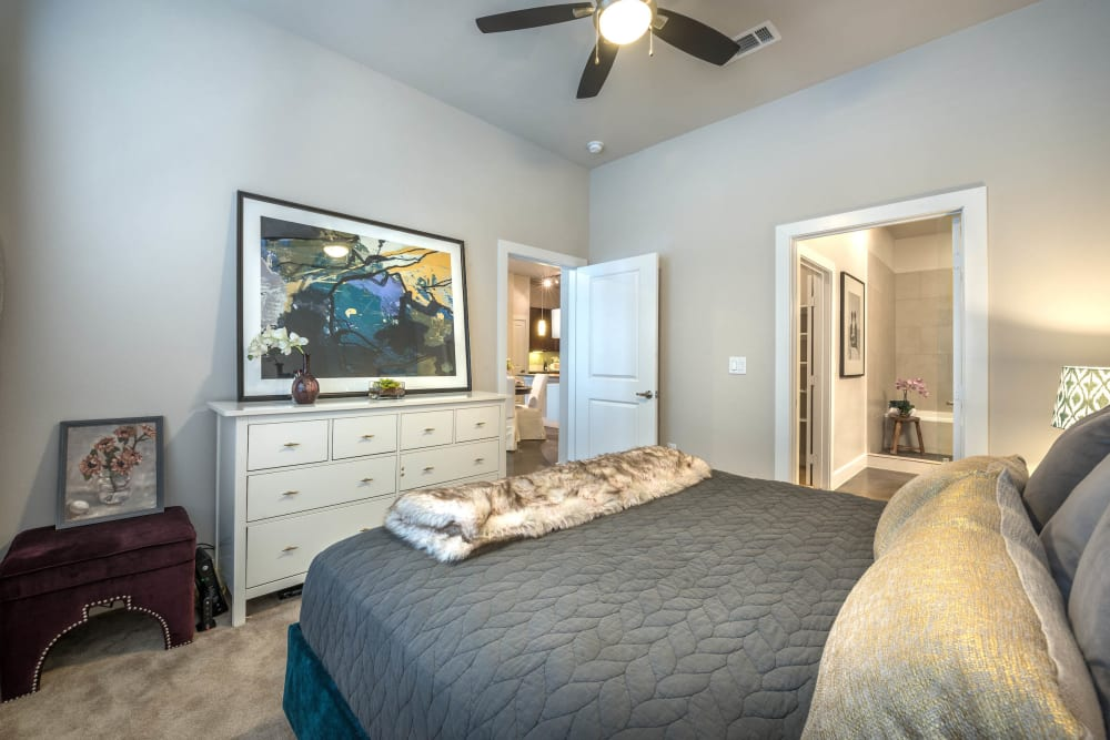 Master bedroom with a ceiling fan and an en suite bathroom in a model home at Olympus at Ross in Dallas, Texas