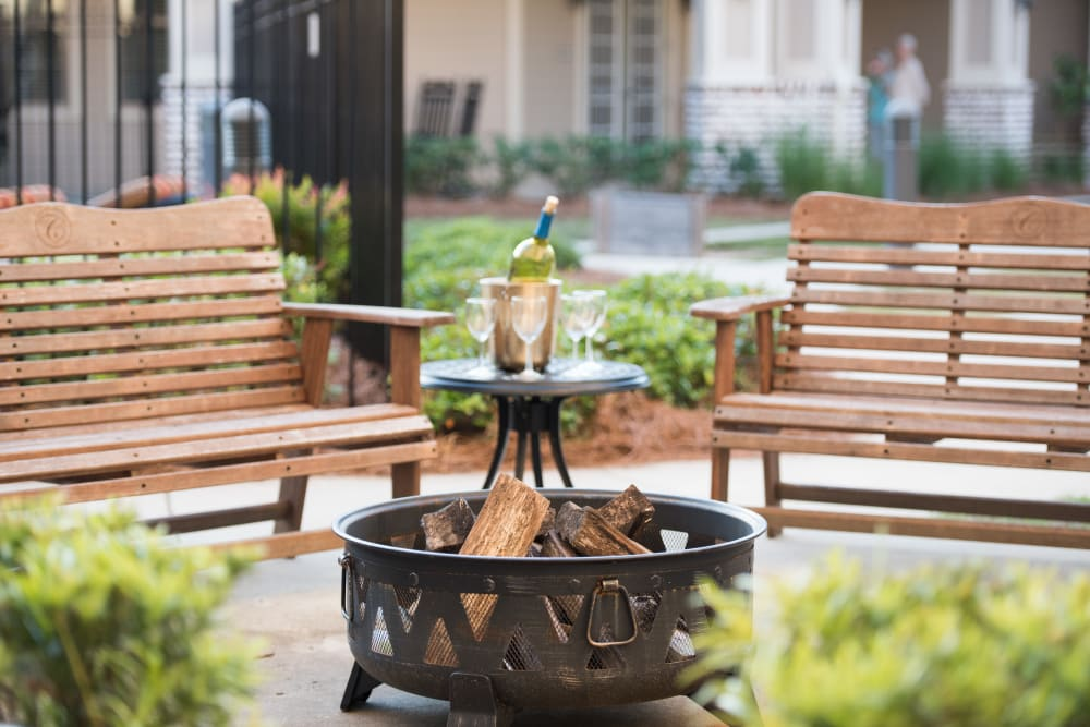 Park benches and fire pit at The Claiborne at Hattiesburg Independent Living in Hattiesburg, Mississippi