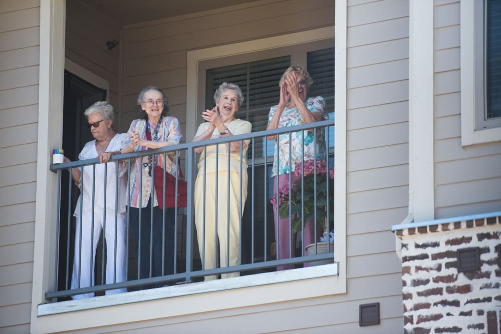 Several residents standing on a balcony at The Claiborne at Hattiesburg Independent Living in Hattiesburg, Mississippi