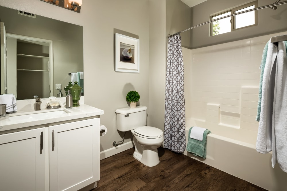 Tiled shower and hardwood flooring in a model home's bathroom at Mission Hills in Camarillo, California