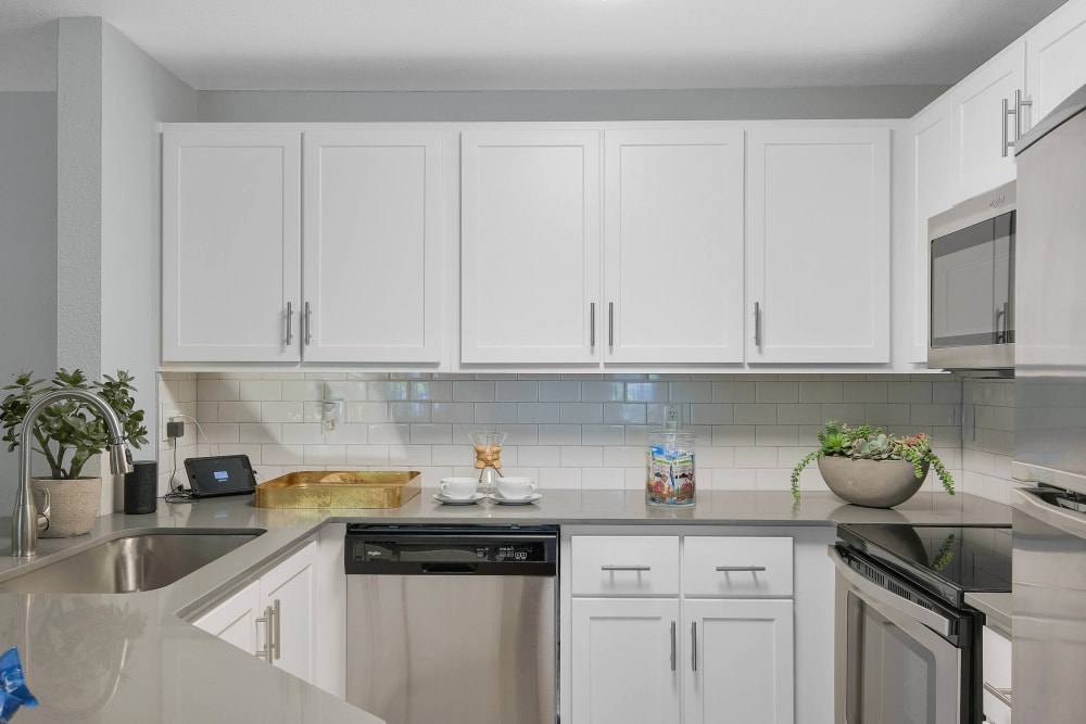 Quartz countertops and white cabinetry in a model home's kitchen at Centro Apartment Homes in Hillsboro, Oregon