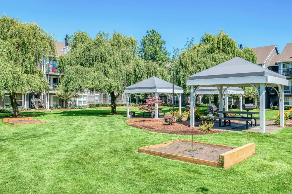 Horseshoes game area with beautiful green grass and shaded seating nearby at Centro Apartment Homes in Hillsboro, Oregon