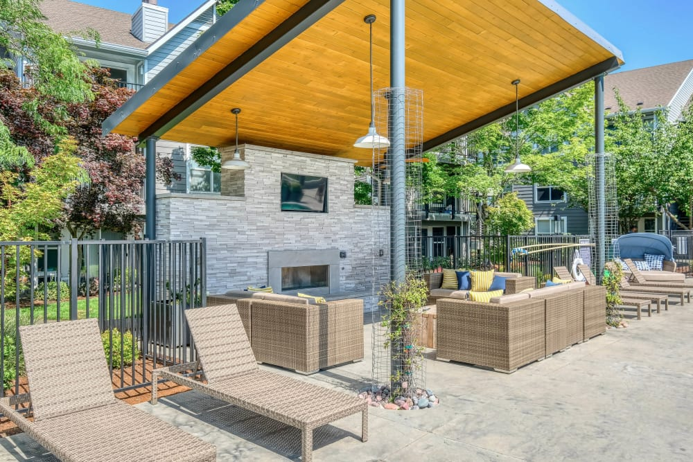 Chaise lounge chairs near the shaded outdoor lounge with a flatscreen TV at Centro Apartment Homes in Hillsboro, Oregon