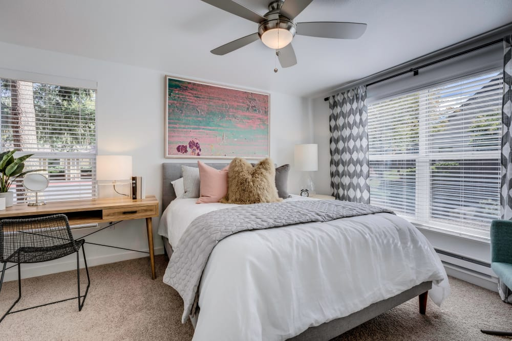 Master bedroom with large bay windows and a ceiling fan in a model home at Centro Apartment Homes in Hillsboro, Oregon