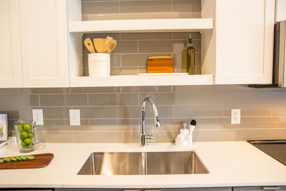 An apartment kitchen sink with backsplash at Belcourt Park in Nashville, Tennessee