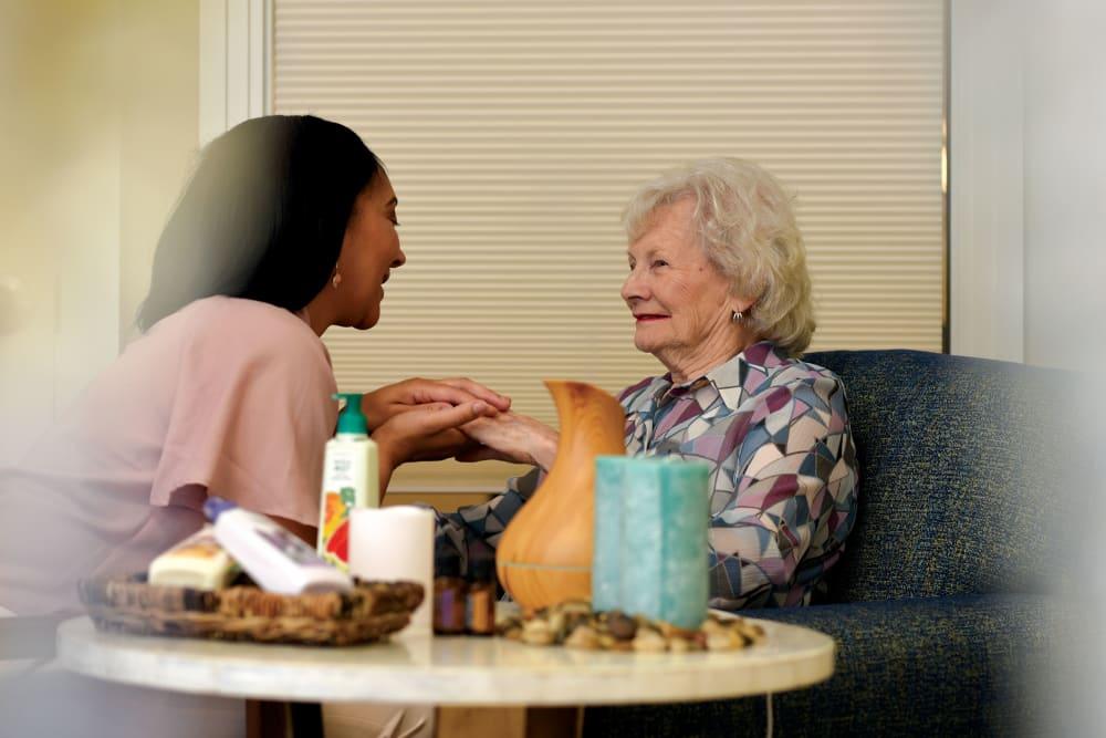Caregiver moisturizing senior woman's hands