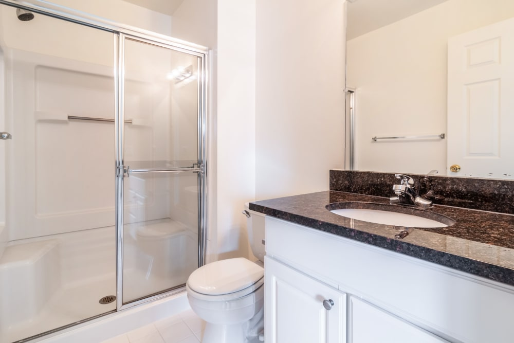 An apartment bathroom with black counter top at Central Park Estates in Novi, Michigan