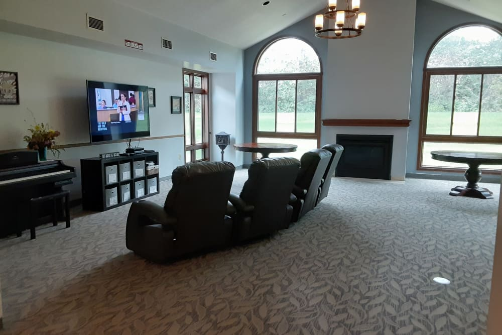 Community room with TV and piano at The Atrium in Rockford, Illinois.