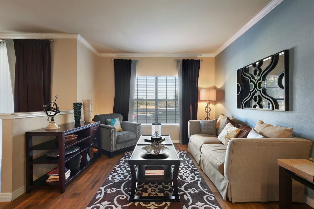 Bright, spacious living room with hardwood flooring at The Lyndon in Irving, Texas