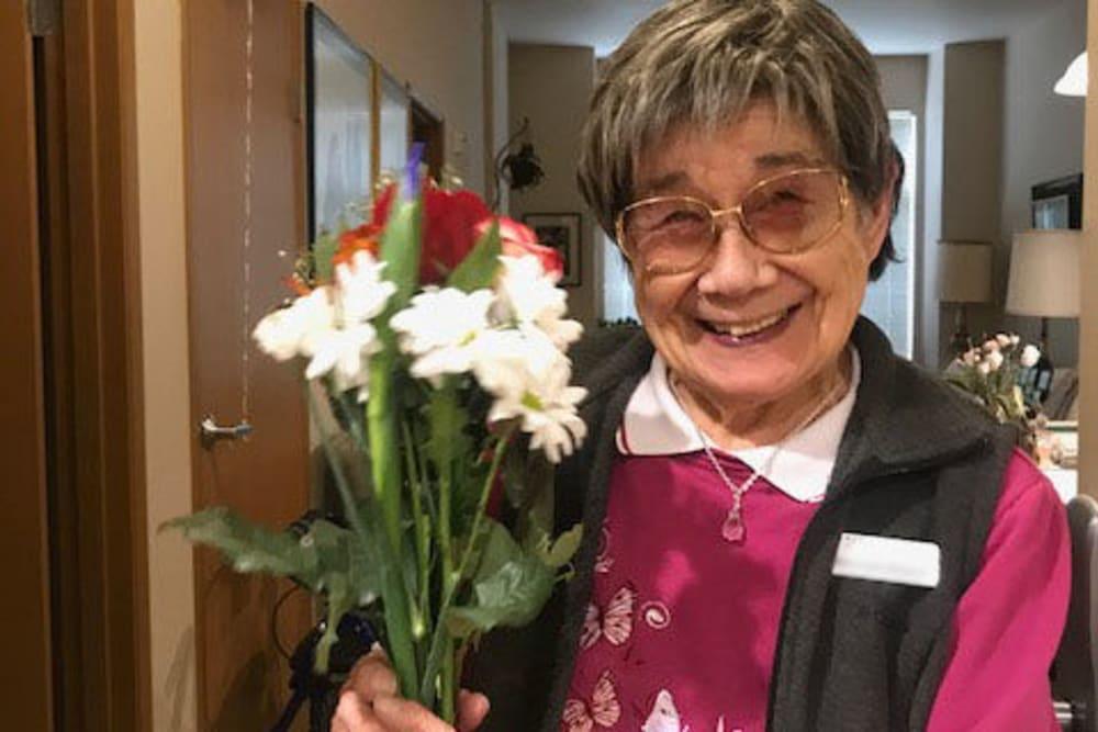A Merrill Gardens resident holding flowers.