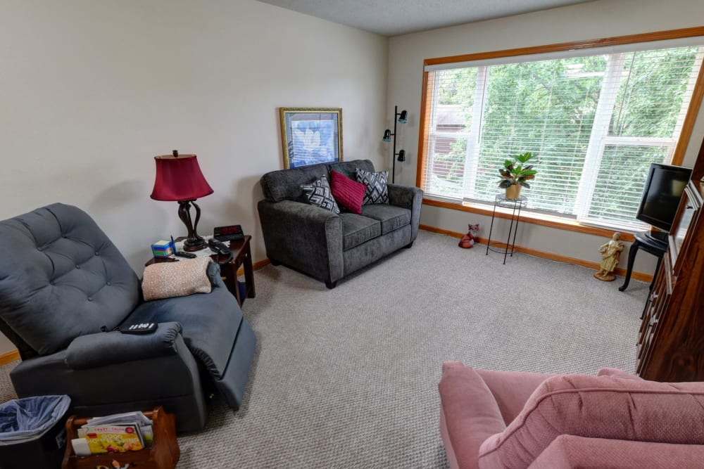 Resident living room with large windows at Garnett Place in Cedar Rapids, Iowa.
