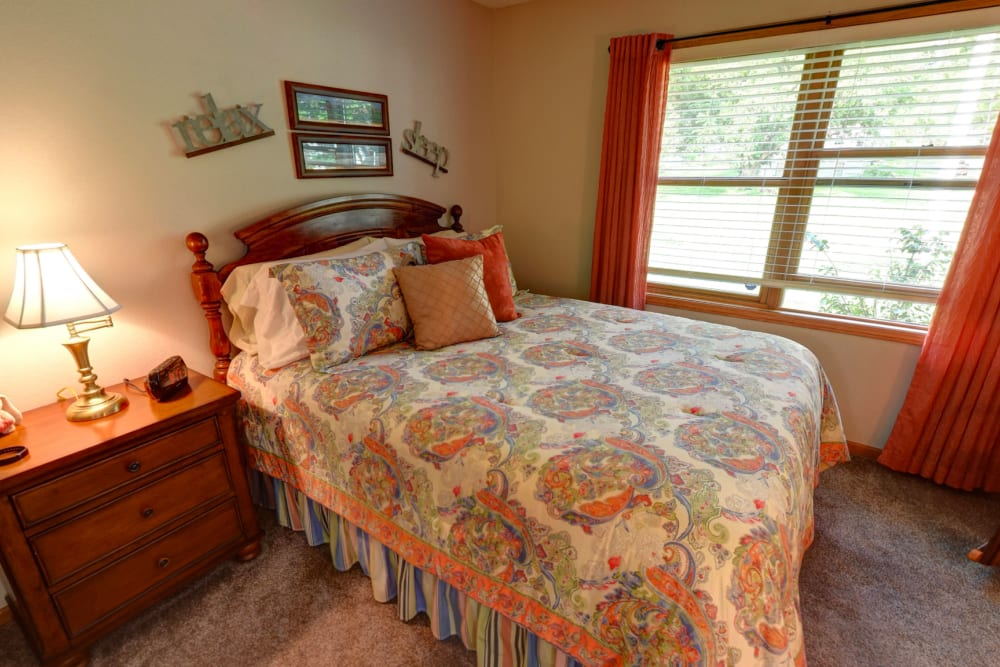 Resident bedroom with a side table and wall art at Garnett Place in Cedar Rapids, Iowa.