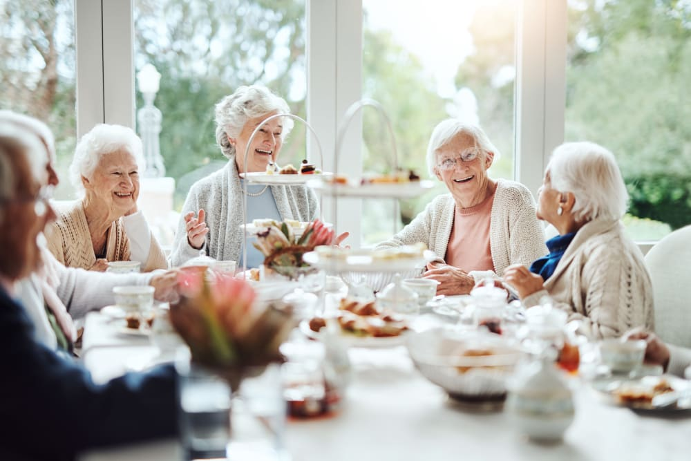 Group of women residents enjoying brunch at Avenir Memory Care Westside in Los Angeles, California.