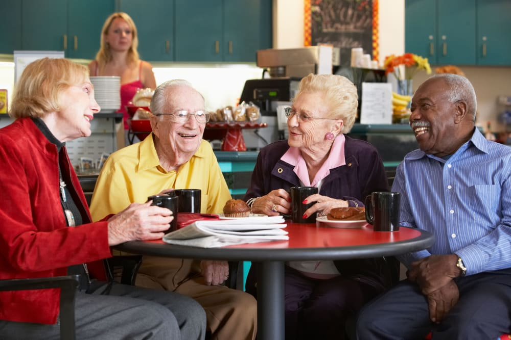 Group of residents talking over coffee and muffins at Avenir Memory Care Westside in Los Angeles, California.