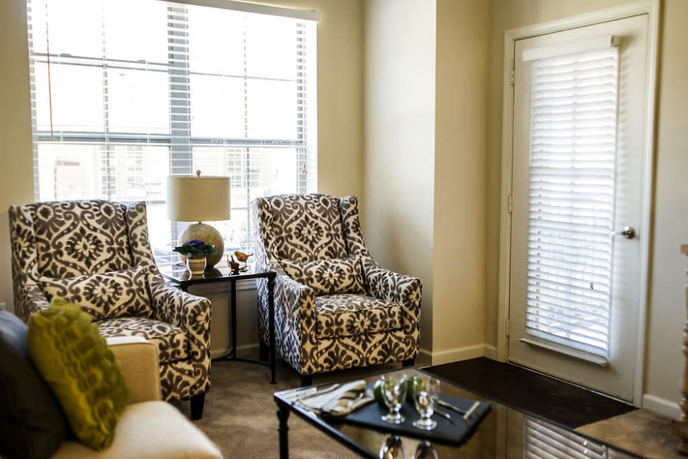View of the living room and door to the balcony at The Claiborne at Hattiesburg Independent Living in Hattiesburg, Mississippi