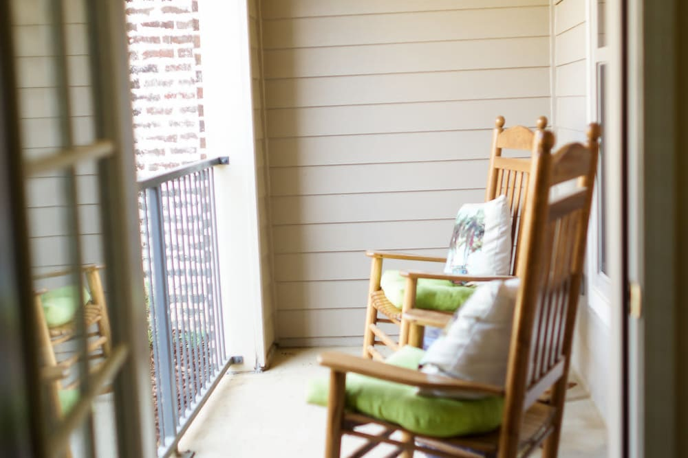 View of rocking chairs on a balcony at The Claiborne at Hattiesburg Independent Living in Hattiesburg, Mississippi
