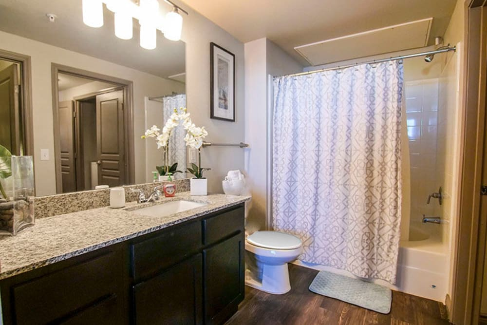 Granite countertop and a large vanity mirror in a model home's bathroom at Anatole on Briarwood in Midland, Texas
