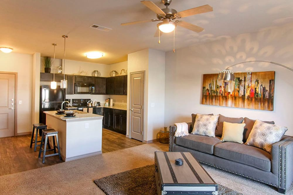 Open-concept living area with a ceiling fan and plush carpeting in a model home at Anatole on Briarwood in Midland, Texas