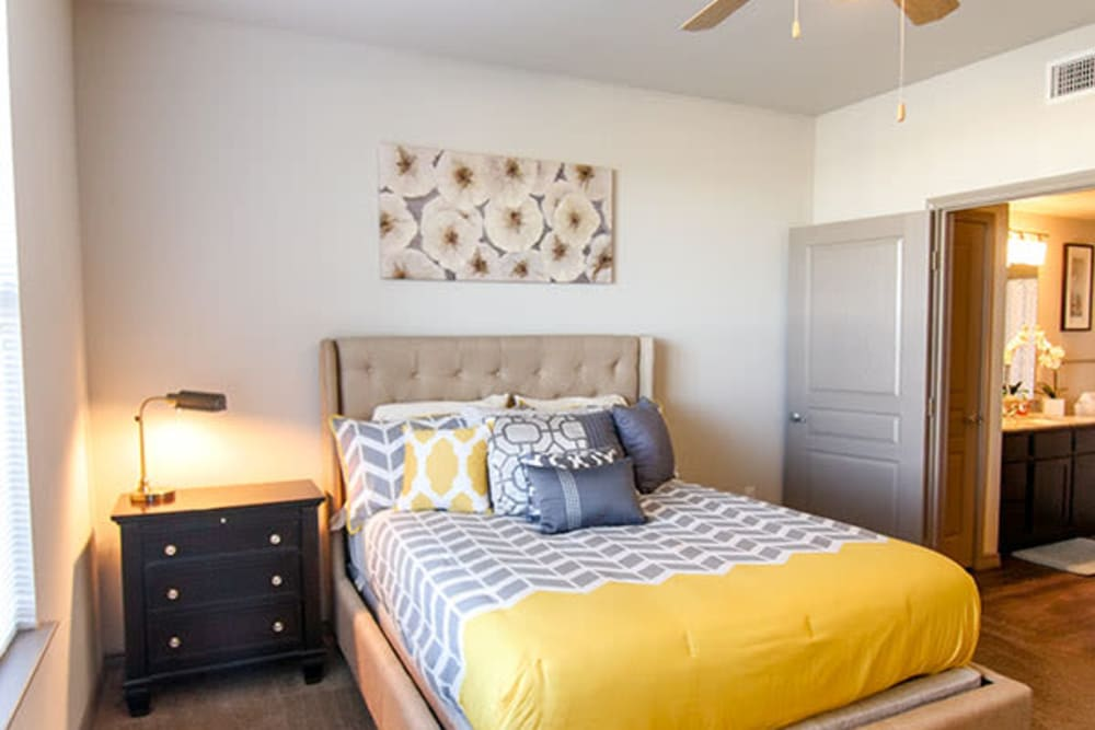 Master bedroom with an en suite bathroom in a model home at Anatole on Briarwood in Midland, Texas