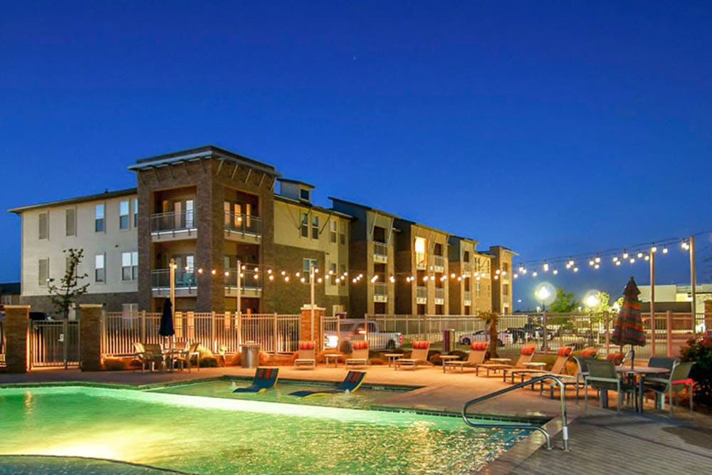 Evening view of the swimming pool with underwater lights on at Anatole on Briarwood in Midland, Texas