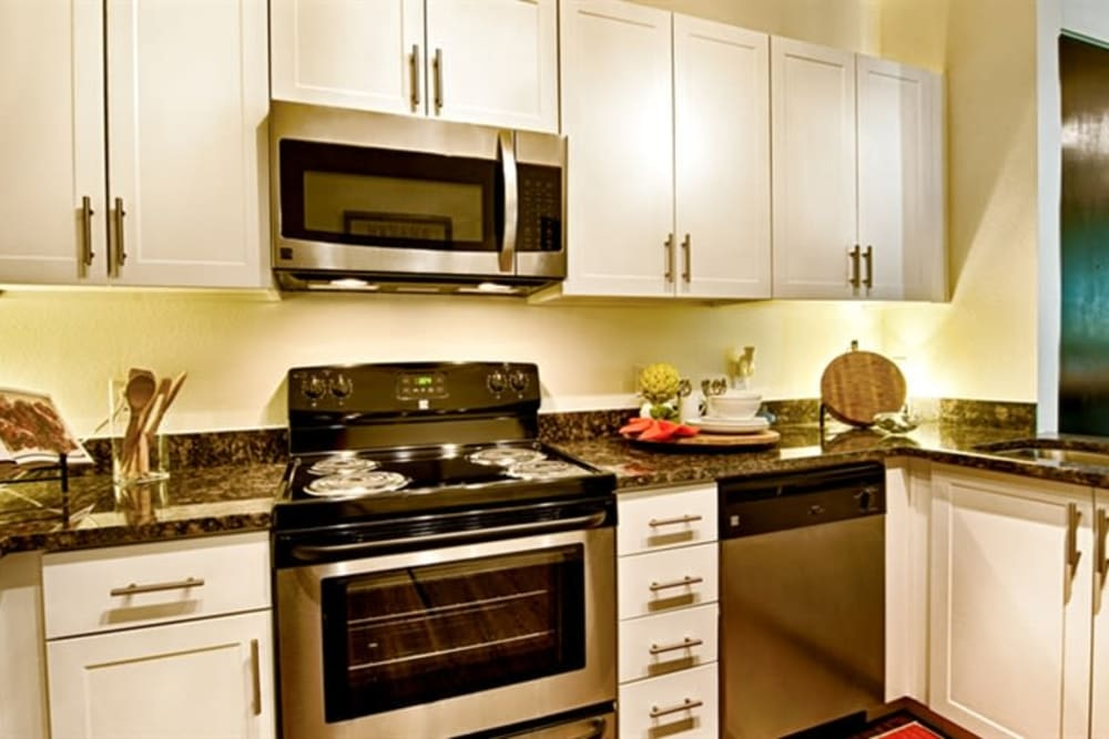 White cabinetry and stainless-steel appliances in a model home's kitchen at Cactus Forty-2 in Phoenix, Arizona