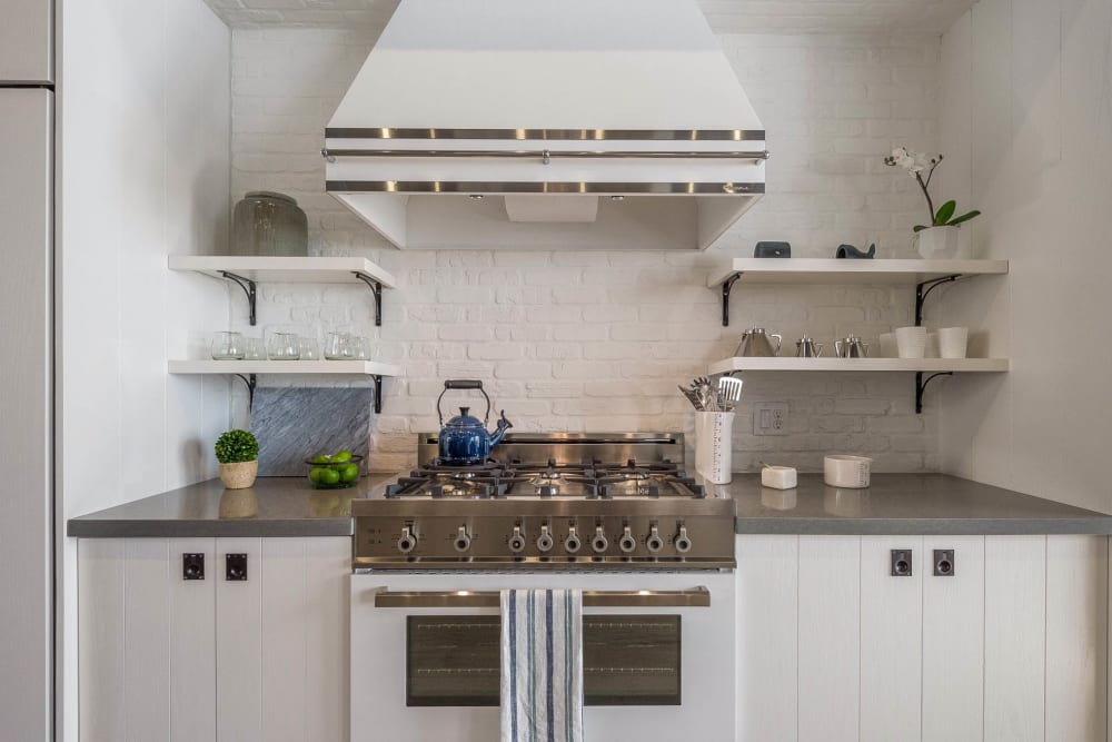 Gourmet kitchen with granite countertops and bright white cabinetry in a model home at Cadia Crossing in Gilbert, Arizona