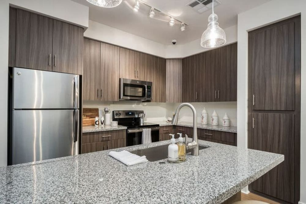 Stainless-steel appliances and custom wood cabinetry in the gourmet kitchen of a model home at Cadia Crossing in Gilbert, Arizona