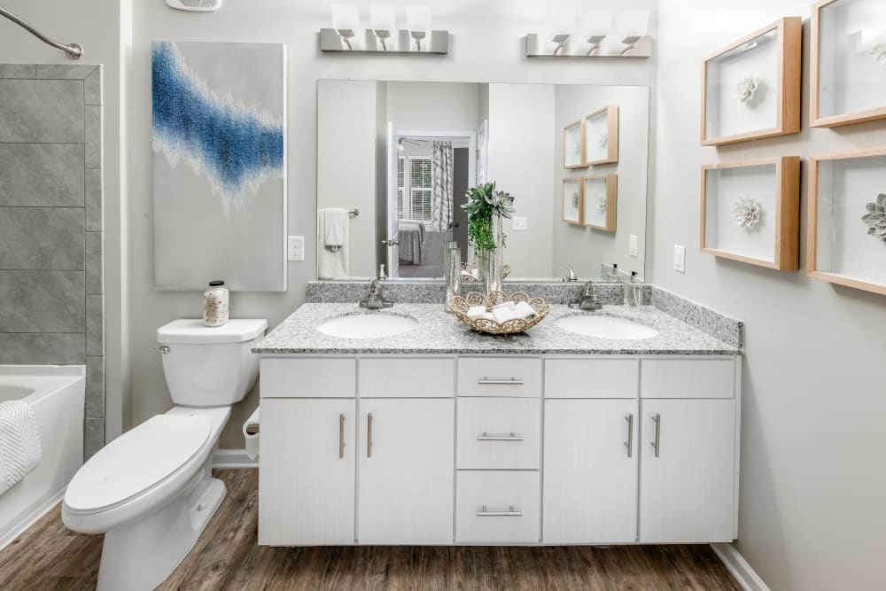 Dual sinks and a granite countertop in a model home's bathroom at Canopy at Citrus Park in Tampa, Florida