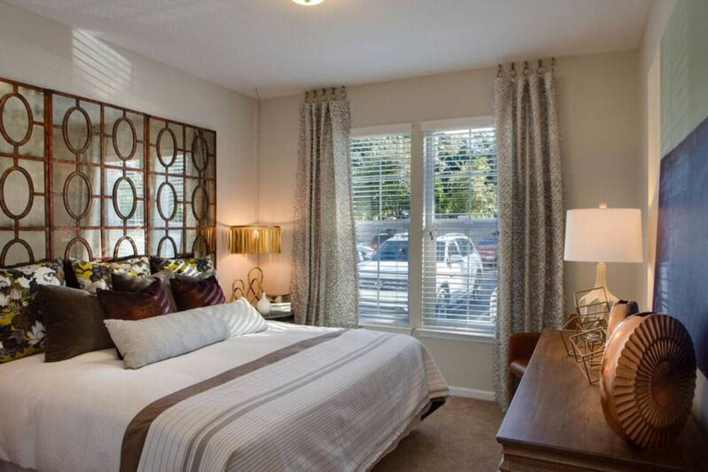 Draped windows and fine furnishings in the master bedroom of a model home at Canopy at Citrus Park in Tampa, Florida