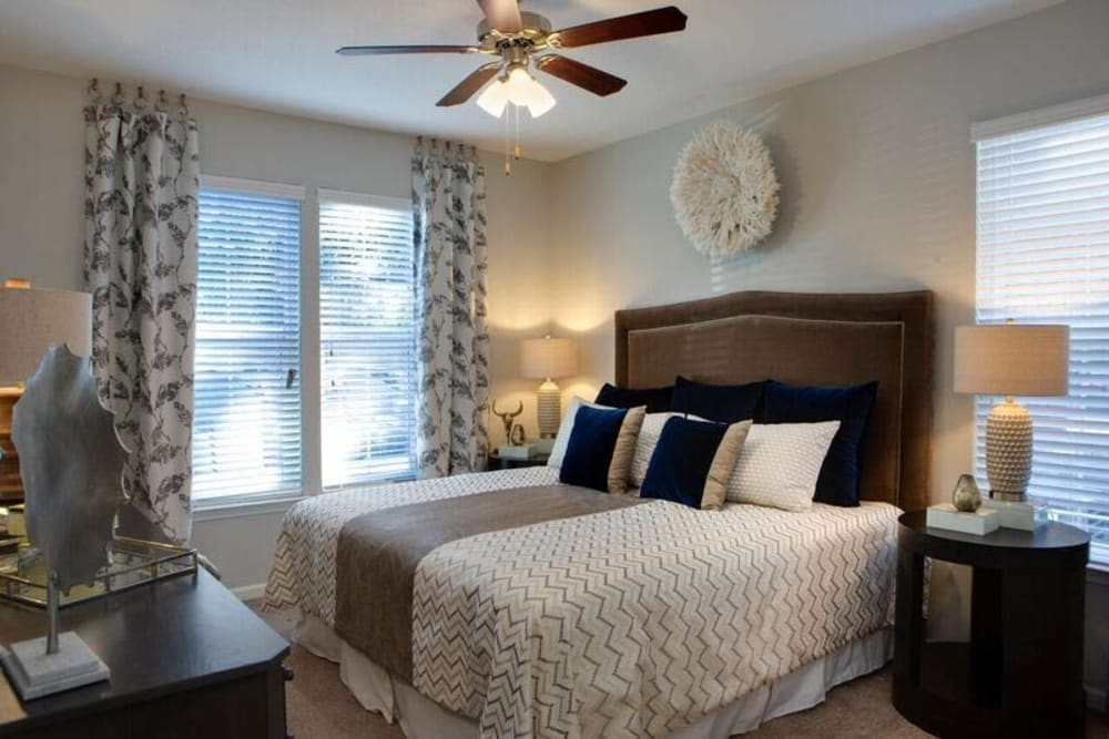 Ceiling fan and modern furnishings in a model home's master bedroom at Canopy at Citrus Park in Tampa, Florida