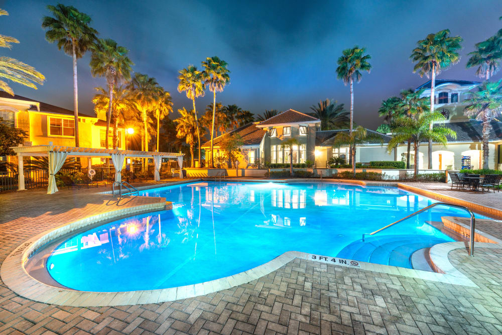 Swimming pool lit up with underwater lighting in the evening at Cape House in Jacksonville, Florida