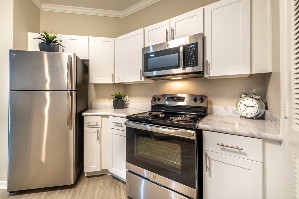 Gourmet kitchen with bright white cabinetry and stainless-steel appliances in a model home at Cape House in Jacksonville, Florida
