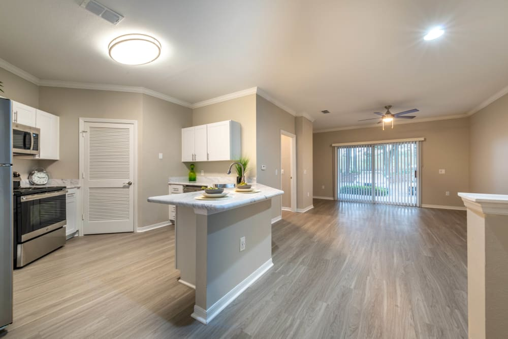 Island with a granite countertop in the open-concept kitchen of a model home at Cape House in Jacksonville, Florida