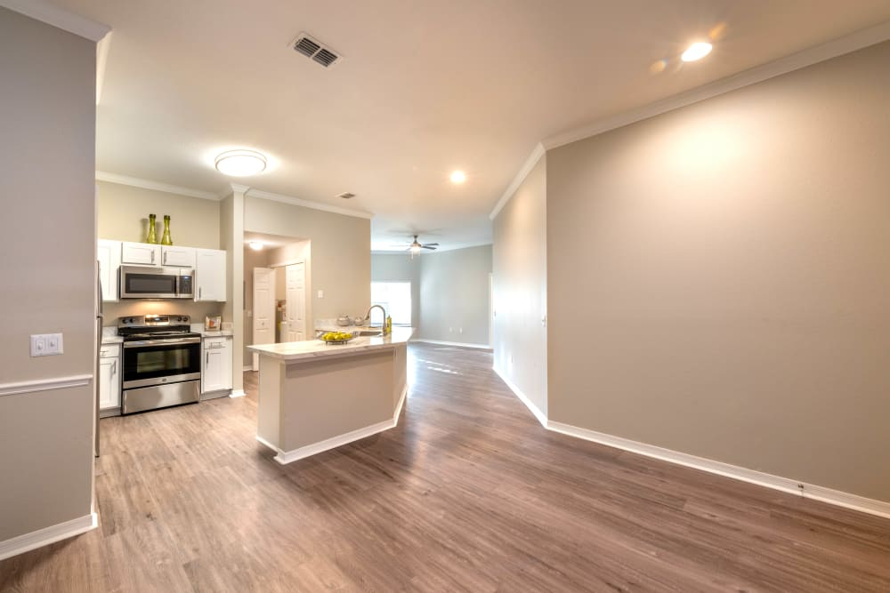 Large open-concept layout with hardwood flooring in a model home at Cape House in Jacksonville, Florida
