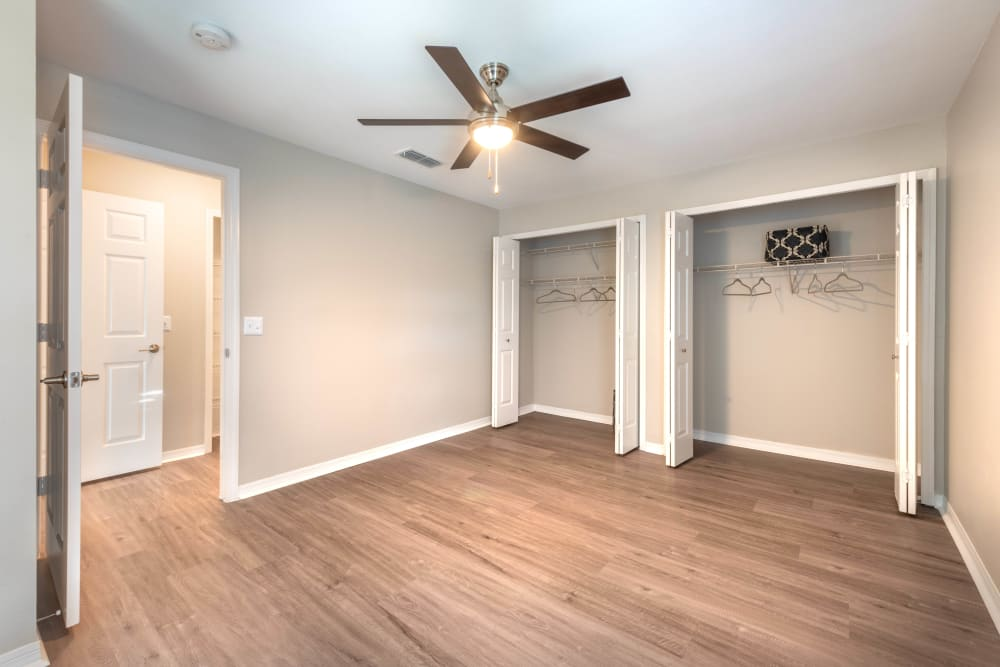 Hardwood flooring, a ceiling fan, and ample closet space in a model apartment's bedroom at Cape House in Jacksonville, Florida