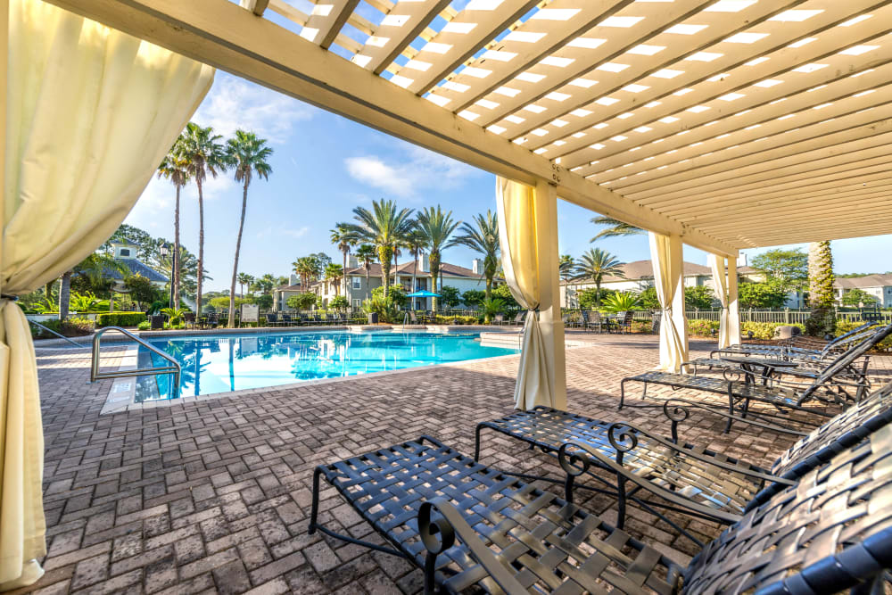 Pergola providing partial shade to the lounge chairs by the pool at Cape House in Jacksonville, Florida