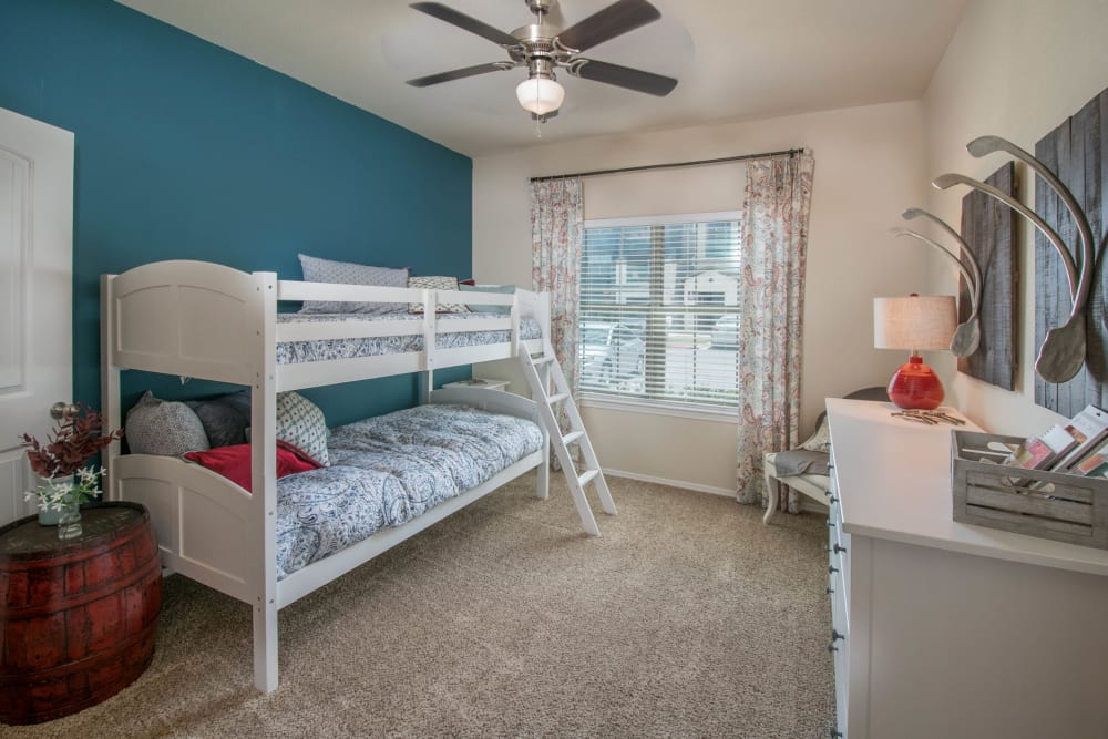 Plush carpeting and a ceiling fan in a model home's child's room at Carrington Oaks in Buda, Texas